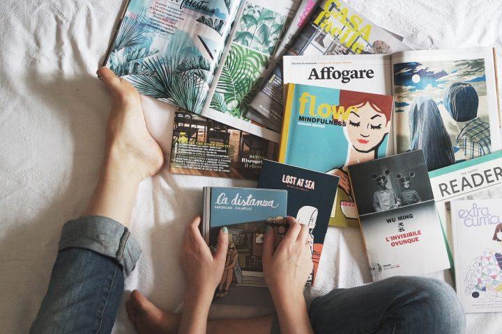 na foto, mãos de uma pessoa segurando um livro e vários livros na cama. quarentena em casa